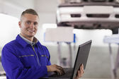 Mecânico sorridente usando um laptop — Foto Stock