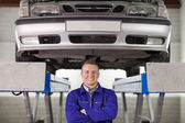 Mechanic with arms crossed below a car — Stock Photo