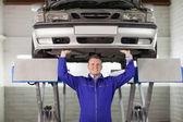 Smiling mechanic touching the below of a car — Stock Photo