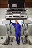Smiling mechanic standing below a car — Stock Photo