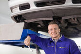Mechanic holding a spanner below a car — Stock Photo