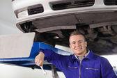 Mechanic holding a spanner below a car — Stock Photo