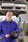 Smiling mechanic holding a tablet computer — Stock Photo