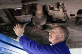 Mechanic repairing the below of a car — Stock Photo