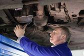Mechanic repairing the below of a car — Stock Photo