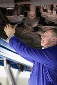 Mechanic repairing the below of a car with a spanner — Stock Photo