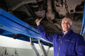 Smiling mechanic repairing with a spanner — Stock Photo