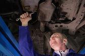 Smiling mechanic repairing the below of a car — Stock Photo