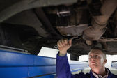Concentrated mechanic repairing the below of a car — Stock Photo