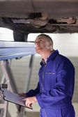 Mechanic looking at the below of a car — Stock Photo