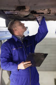 Mechanic looking at the below of a car while holding a clipboard — Stock Photo