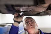 Mechanic illuminating the car with a flashlight — Stock Photo