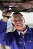 Mechanic illuminating the below of a car — Stock Photo