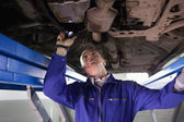Mechanic looking the below of a car while holding a flashlight — Foto Stock