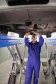 Mechanic standing while repairing the below of a car — Stock Photo