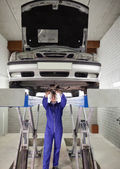 Mechanic standing while repairing a car — Stock Photo