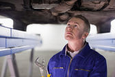 Mechanic looking at the below of a car while holding an adjustab — Stock Photo