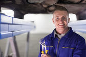 Smiling mechanic holding an adjustable pliers — Stock Photo