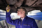 Man looking at the below of a car while repairing — Stock Photo