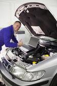 Mecânico consertando um carro com um computador — Foto Stock