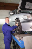 Mechanic standing while repairing a car wheel — Stock Photo