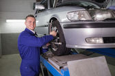 Smiling mechanic standing while repairing a car wheel — Stock Photo
