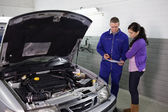 Mechanic holding a clipboard next to a woman — Stock Photo