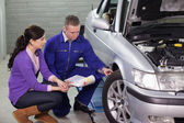 Mechanic showing the car wheel to a client — Stock Photo