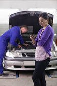 Woman looking a her mobile phone next to a mechanic — Fotografia Stock