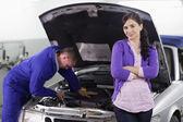 Mujer apoyándose en un auto junto a un mecánico — Foto de Stock