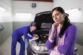 Thoughtful woman next to a mechanic — Stockfoto