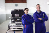 Smiling mechanics with arms crossed — Stock Photo