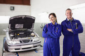 Smiling mechanics with arms crossed next to a car — Stock Photo