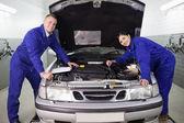Mechanica leunend op een auto — Stockfoto