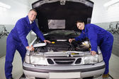 Mechanics leaning on a car — Stockfoto