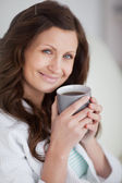 Woman holding a mug of coffee while looking at camera — Stock Photo