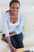 Black woman smiling while sitting on a sofa — Stock Photo