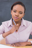 Black teacher looking at camera while thinking — Stock Photo