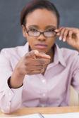 Stränga läraren pekar finger medan röra hennes glasögon — Stockfoto