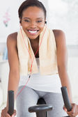 Black woman on an exercise bike listening music — Stok fotoğraf