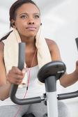 Concentrated woman doing exercise bike while listening music — Stock Photo