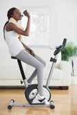 Vista laterale di una donna nera su una cyclette — Foto Stock