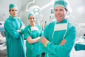 Surgical team with arms crossed smiling — Stock Photo