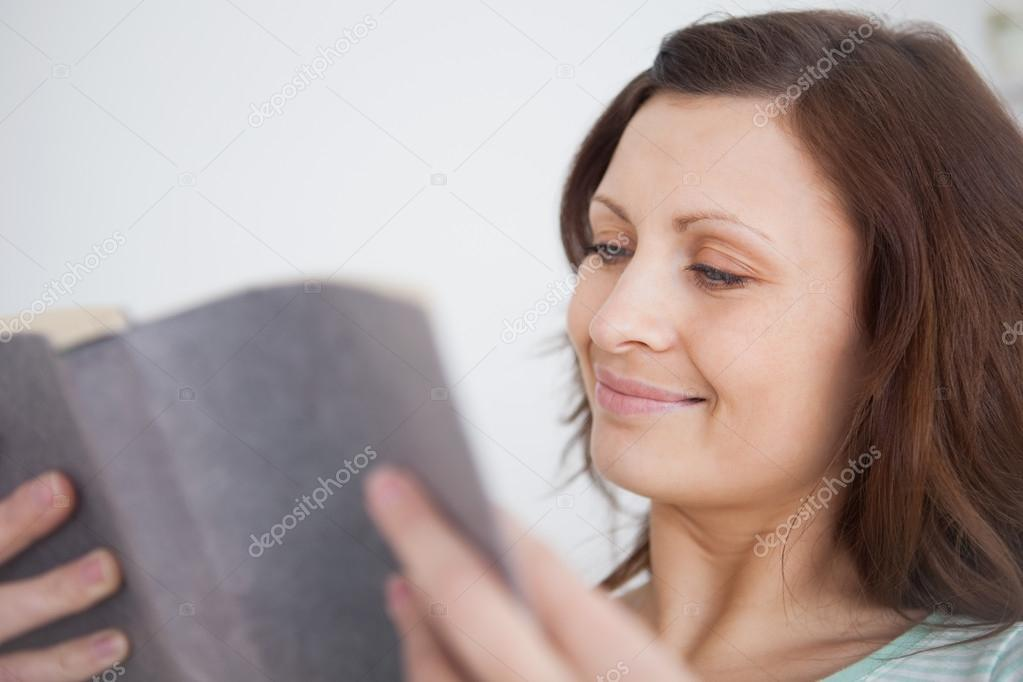 Woman looking at a book in a living room  Stock Photo #14154193