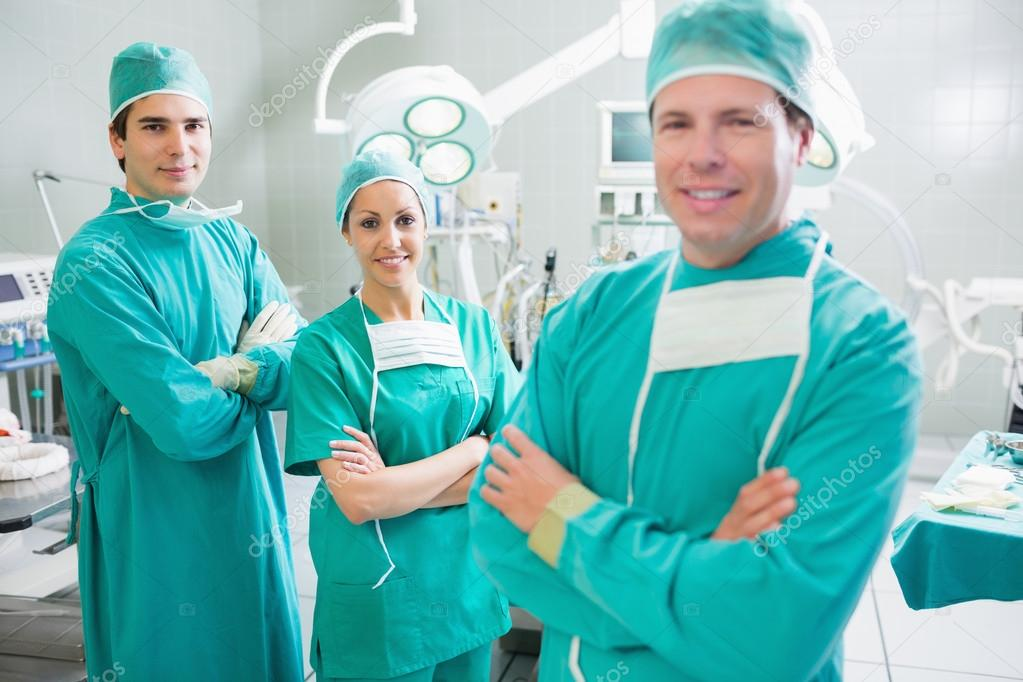 Surgical team with arms crossed smiling in an operating theatre — Stock fotografie #14156293