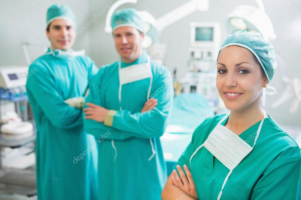 Surgical team with arms crossed in an operating theatre — Stock Photo #14156301