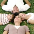 Smiling family lying in a park with heads together - Stock Photo