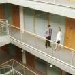 Stockvideo: Businessman and businesswoman interacting in a big building