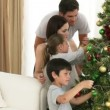 Royalty-Free Stock Vector Image: Young family decorating a Christmas tree together