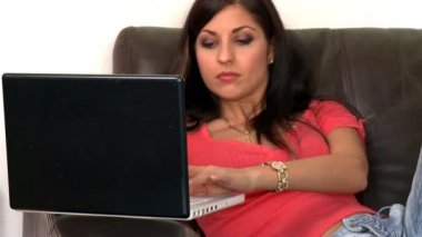 Charming woman using a laptop sitting on sofa — Stock Video